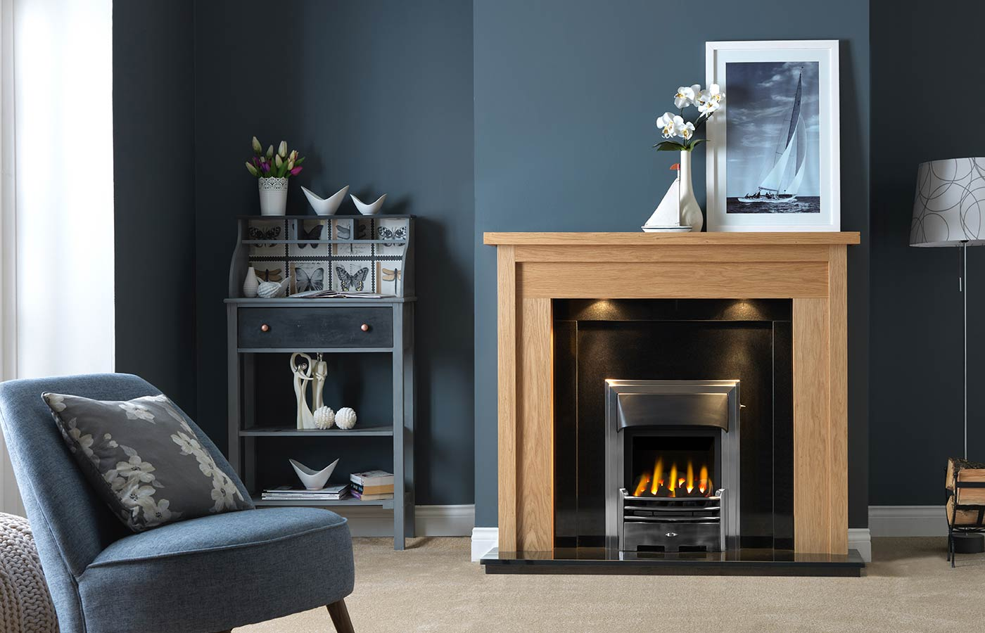 Askham Fireplace Suite in Light Oak Veneered MDF complete with Back Panel and Hearth in Ebony Granite, shown with Gallery Baltimore in Chrome Finish with Glass-Fronted Gas Convector Fire