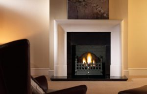 """Delection 56"""" Agean limestone mantel with Castle fire basket in black, decorative gas fire with ceramic coal, granite slips, black painted reeded fireboard chamber, 60"""" slabbed granite hearth and slabbed granite back hearth"""